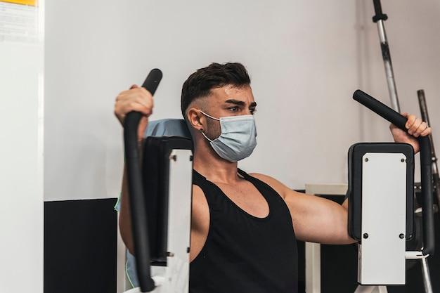 Chłopiec z maską robi ćwiczenia klatki piersiowej w siłowni