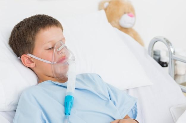 Chłopiec z maską tlenową w łóżku