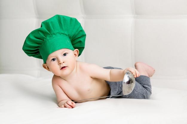 Chłopiec z metalową kopyścią i kucharza kapeluszem