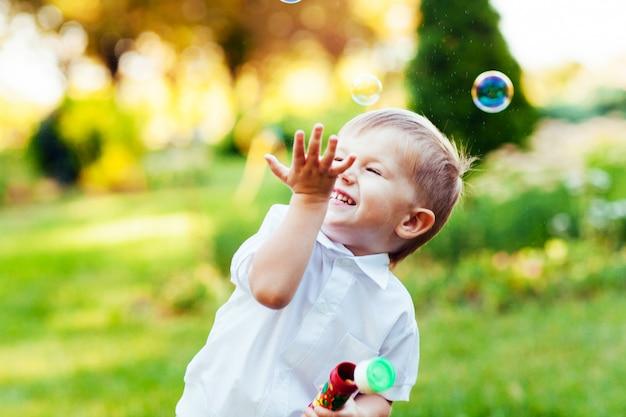 Chłopiec z mydlanymi bąblami w lato parku.
