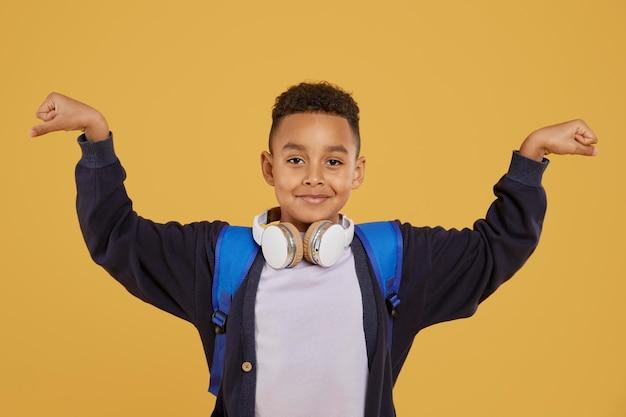 Chłopiec z niebieskim plecakiem pokazującym mięśnie