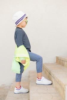 Chłopiec z okularami przeciwsłonecznymi na schodkach