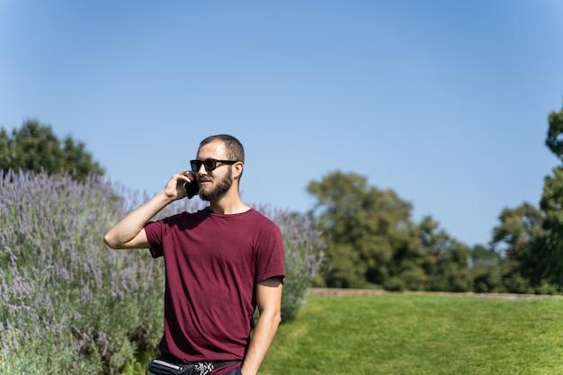 Chłopiec z okularami przeciwsłonecznymi po środku ogródu opowiada na telefonie komórkowym