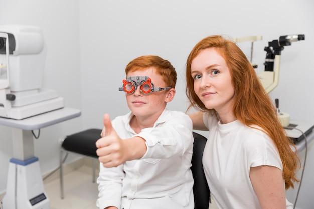 Chłopiec z optometrist próby ramą pokazuje kciuka gesta up obsiadanie z młodym żeńskim okulistą w klinice