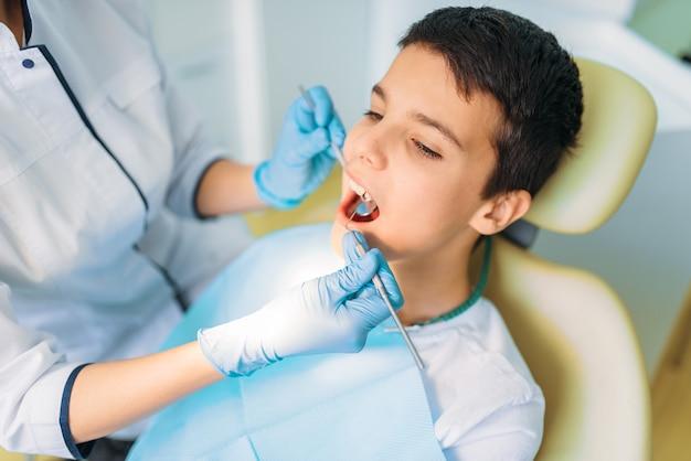 Chłopiec z otwartymi ustami w fotelu dentystycznym