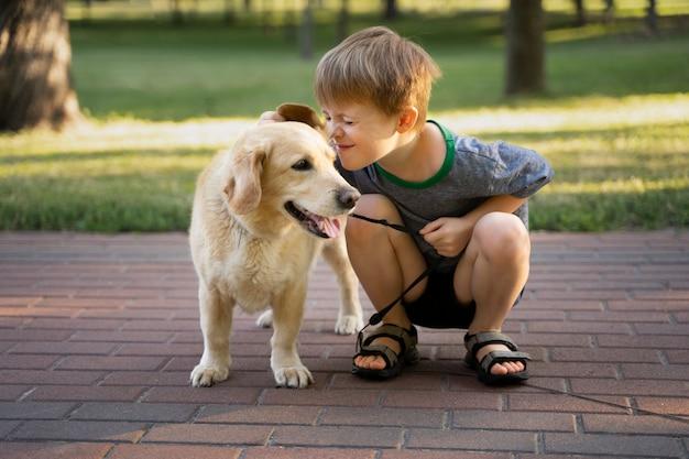 Chłopiec z pełnym strzałem i uśmiechnięty pies