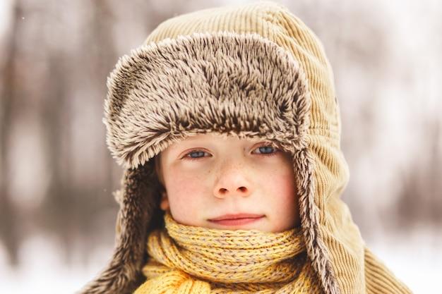 Chłopiec z piegami w puszystej czapce zimowej w przyrodzie