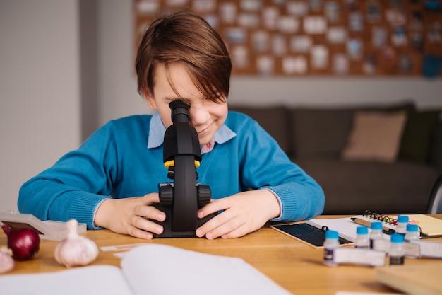 Chłopiec z pierwszej klasy uczący się w domu przy użyciu mikroskopu