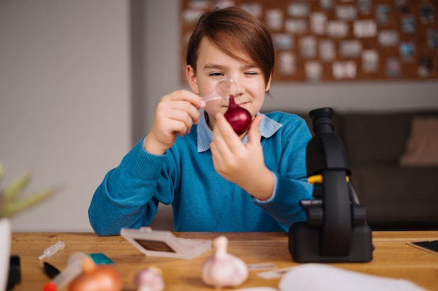 Chłopiec z pierwszej klasy uczy się w domu, robi eksperymenty