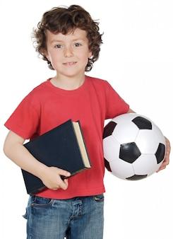 Chłopiec z piłką i książką odizolowywającymi na bielu