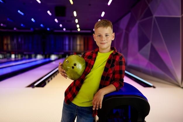 Chłopiec z piłką pozuje na torze w kręgielni
