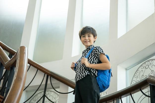 Chłopiec z plecak stojący po schodach po powrocie ze szkoły