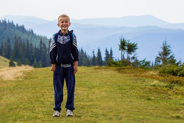 Chłopiec z plecakiem wycieczkuje w scenicznym lato zieleni karpackich górach. dziecko stoi samotnie cieszący się krajobrazowego widok górskiego. aktywny tryb życia, przygoda i aktywność weekendowa.