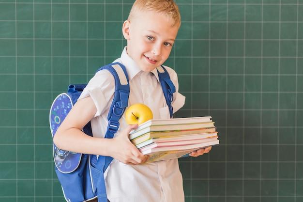 Chłopiec z podręcznikami i plecakiem blisko chalkboard