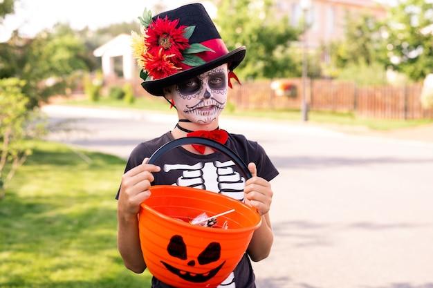 Chłopiec z pomalowaną twarzą w czarnej halloweenowej koszulce i eleganckim kapeluszu trzymający plastikowy koszyk ze słodyczami podarowanymi przez ludzi z wiejskich domów
