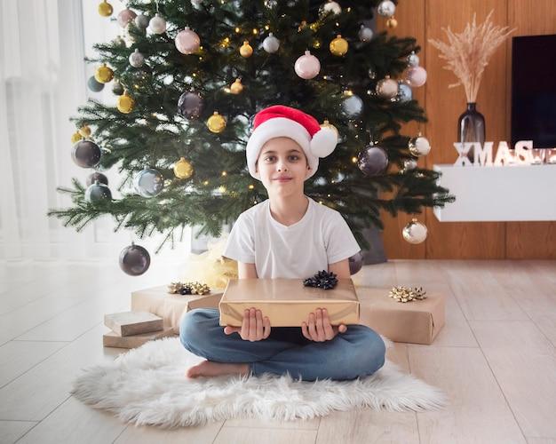 Chłopiec z prezentami gra w pobliżu choinki. wnętrze salonu z choinką i dekoracjami. nowy rok. rozdawanie prezentów.