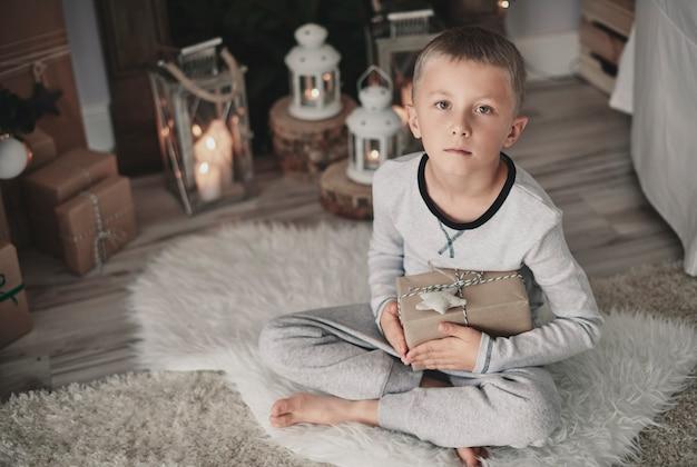 Chłopiec z prezentem w kucki na dywanie w domu