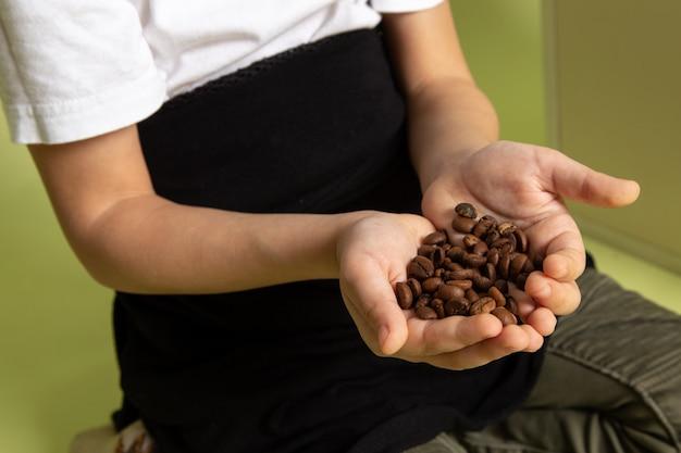 Chłopiec z przodu trzyma kawowe brązowe nasiona w białej koszulce na kamiennym biurku