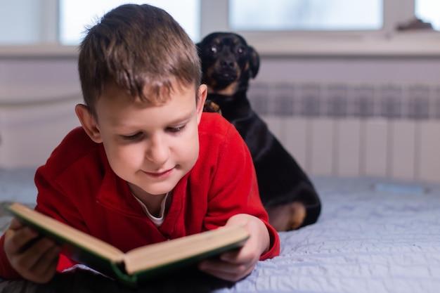 Chłopiec z psem czyta książkę