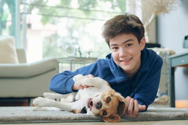 Chłopiec z psem dziecka. dzieci bawią się ze szczeniakiem. mały chłopiec i beagle na kanapie. zwierzę domowe w domu. opieka nad zwierzętami.