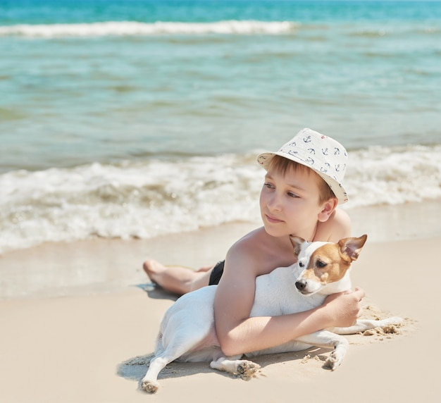 Chłopiec z psim dźwigarki russel na plaży