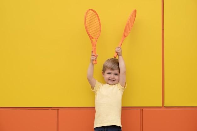 Chłopiec z rakietami tenisowymi przeciw żółtej ścianie