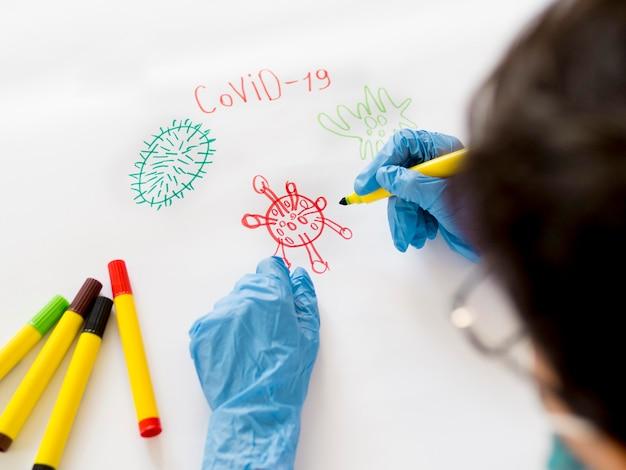 Chłopiec z rękawiczkami rysuje w domu