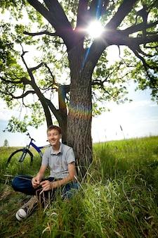 Chłopiec z rowerem w parku na trawie