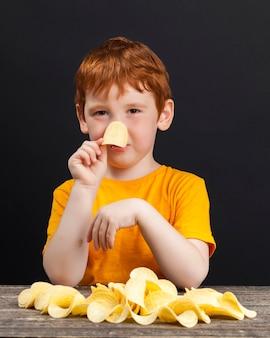 Chłopiec z rudymi włosami je i zbiera chrupiące, pyszne chipsy ziemniaczane podczas jedzenia, niezdrowe jedzenie ziemniaczane, złote chipsy dla chłopca