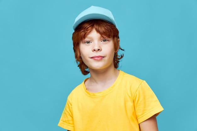 Chłopiec z rudymi włosami portret chłopca w niebieskiej czapce żółty t-shirt studio styl życia
