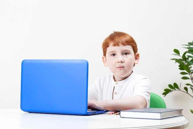 Chłopiec z rudymi włosami, pracujący na komputerze lub studiujący, zdjęcie i portret pięknego dziecka