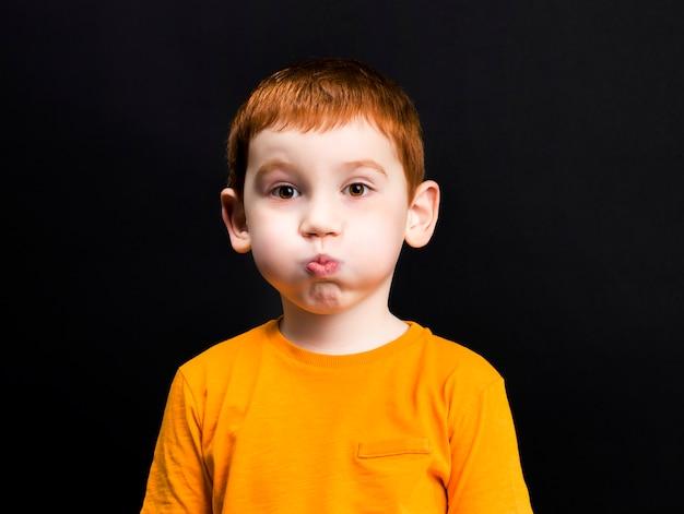 Chłopiec z rudymi włosami wydął policzki, portret chłopca o pięknej twarzy