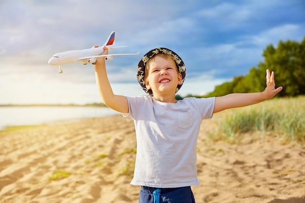 Chłopiec z samolotem w jego rękach na plaży