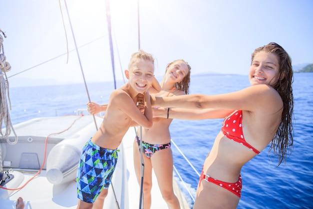Chłopiec z siostrami na pokładzie jachtu na letni rejs. przygoda w podróży, żeglarstwo z dzieckiem na rodzinnych wakacjach.