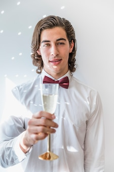 Chłopiec z szampanem przy nowego roku przyjęciem