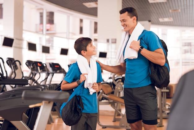 Chłopiec z tatą przyszedł razem na siłownię.