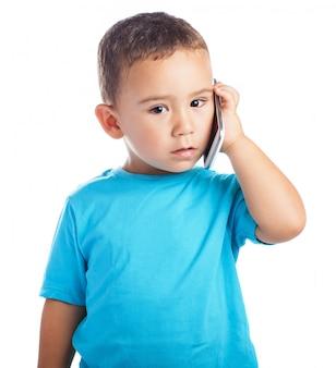 Chłopiec z telefonem w uchu