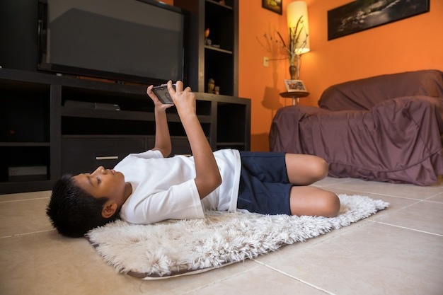 Chłopiec z telefonu komórkowego wideokonferencją w domu