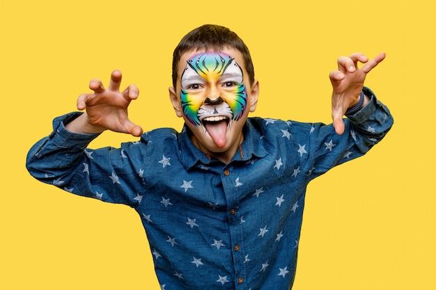 Chłopiec z tygrysim faceart lub aquagrim pozować odizolowywam na kolorze żółtym
