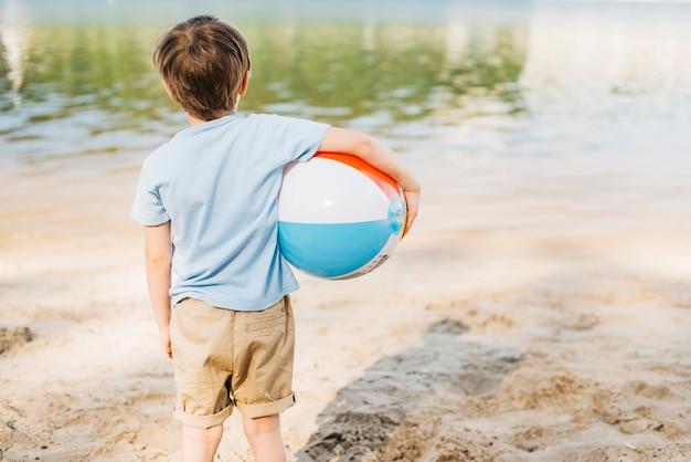 Chłopiec z wiatrową piłką patrzeje wodę