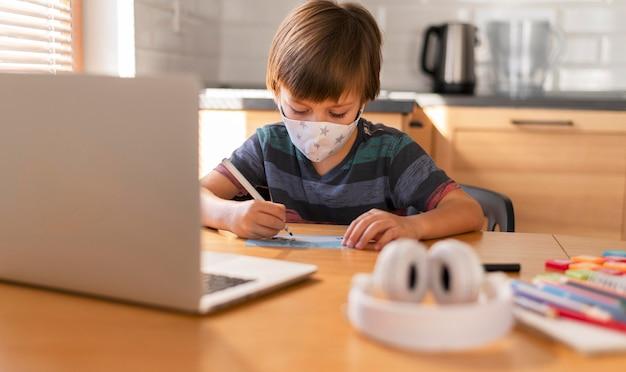 Chłopiec z widokiem z przodu uczący się na lekcjach wirtualnych