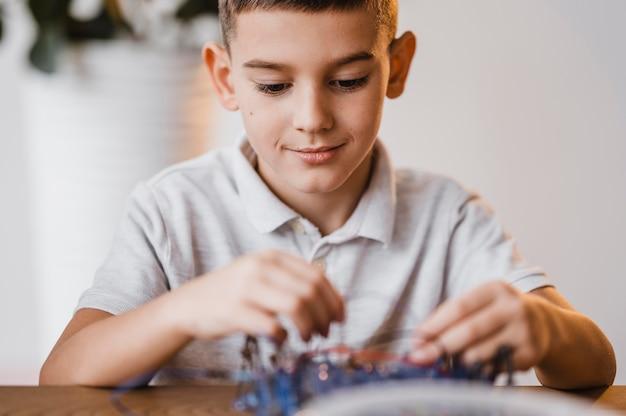 Chłopiec z widokiem z przodu, uczący się o urządzeniach elektrycznych