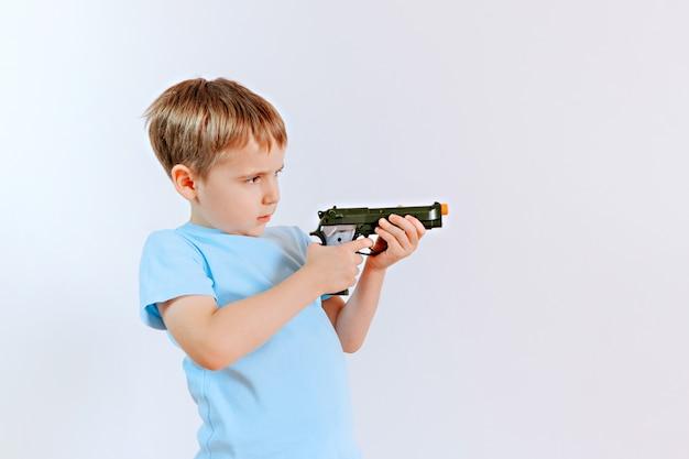 Chłopiec z zabawkarskim klingerytu pistoletem bawić się w domu