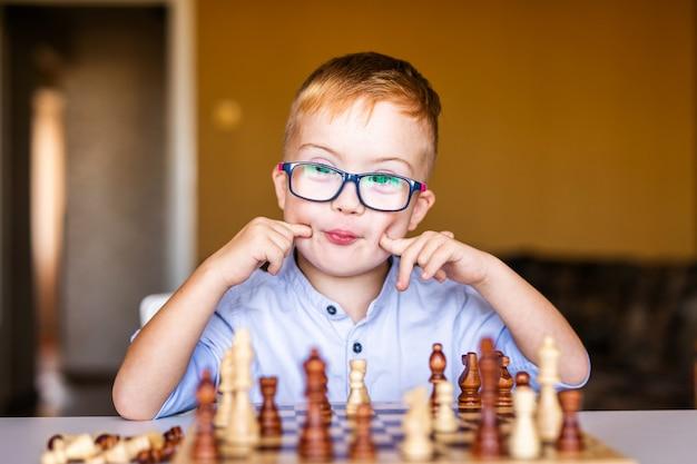 Chłopiec z zespołem downa z dużymi okularami, gra w szachy