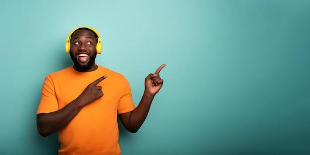 Chłopiec z żółtym zestawem słuchawkowym słucha muzyki i wskazuje coś rękami