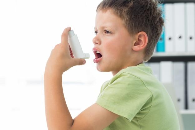 Chłopiec za pomocą inhalatora astmy