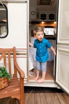 Chłopiec zaglądający za drzwi swojej przyczepy kempingowej