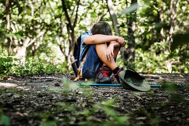 Chłopiec zagubiony i smutny w lesie