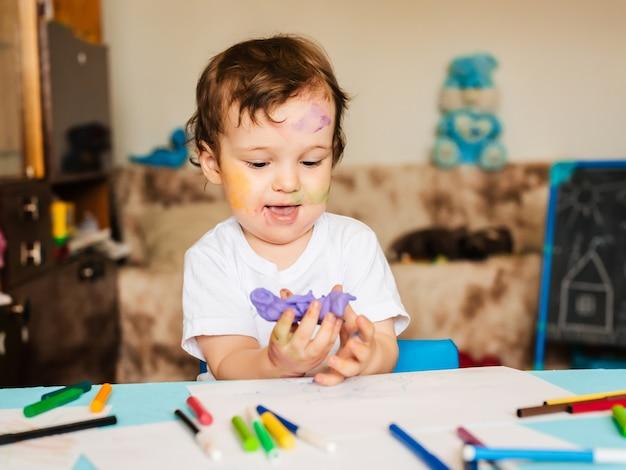 Chłopiec zajmuje się modelowaniem z ciasta do modelowania figur