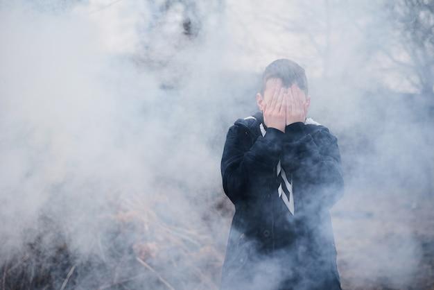 Chłopiec zakrył twarz rękami w gęstym dymie.